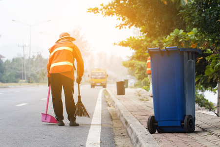 Blue trash bin with worker cleaning the road background on daytime Standard-Bild