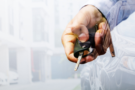 automobile door: Double exposure with car key in hand and car parking in line near the building background