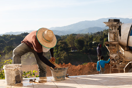 Construction workers making floor with mountain background