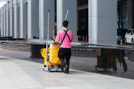 office cleanup: Worker service cleaning with yellow janitorial  interior of building
