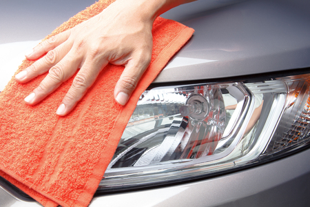 valeting: Close-up of hand cleaning light car with orange cloth Stock Photo