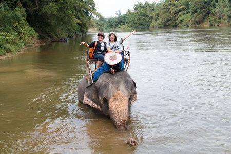 kanchanaburi: Kanchanaburi, THAILAND - JAN 02, 2017: Tourists ride an elephant. Thai elephants used to be one of the main way of transportation for tourists Editorial