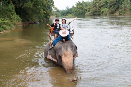 Kanchanaburi, THAILAND - JAN 02, 2017: Tourists ride an elephant. Thai elephants used to be one of the main way of transportation for tourists Editorial