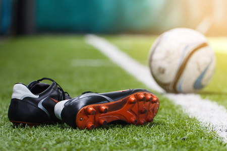 Shoes with blurred soccer ball background on green grass field