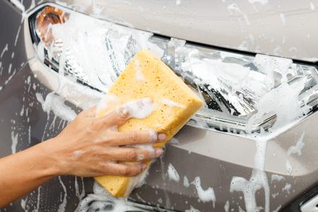 mirror: Closeup photo of employee hand washing car mirror with yellow sponge in car wash shop.