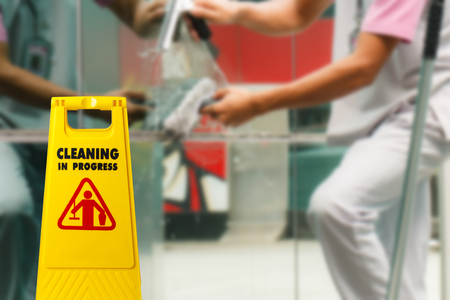 The warning signs cleaning in progress in the building and the maid working in the back. To remind people to walk safely.