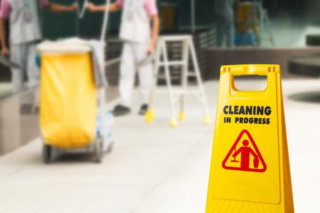 Las señales de advertencia de limpieza en progreso en el edificio y el carro de limpieza con trapeador estacionado y la criada trabajando en la parte posterior. Para recordarles a las personas que caminen de manera segura.