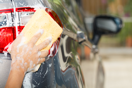 mirror: The rear view photo of employee hand washing car with yellow sponge in car wash shop Stock Photo