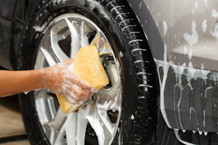employee hand washing car wheel with yellow sponge in car wash shop, selective focus