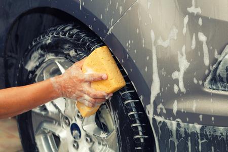 mirror: Closeup photo of employee hand washing car wheel with yellow sponge in car wash shop.
