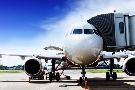 The commercial airplane parked in the airport on blue sky day after the passenger arrives safely at the destination