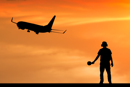 arrives: Silhouette of employee work for airplane departing flight at the airport with orange background