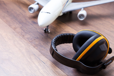 Ear protection on the wooden floor with airplane in back, represents the concept of keeping the quality of hearing