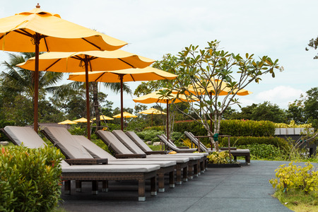 Outdoor beach chairs and yellow umbrellas for holiday vacations in the gardent