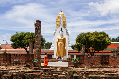 PHITSANULOK, THAILAND-SEPTEMBER 3, 2017: Buddhist worshiping the statues of the great Buddha while the monk pass in daytime on September 3, 2017 in Phitsanulok, Thailand