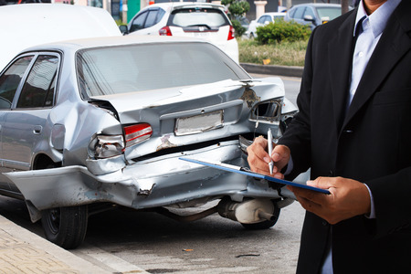 Car insurance agents writing clipboard of car accident-damaged as a proof of insurance claim