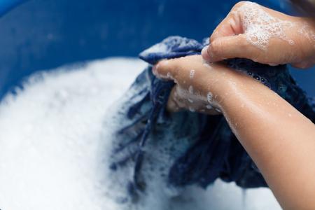 Woman hands washing black clothes in blue basin Foto de archivo
