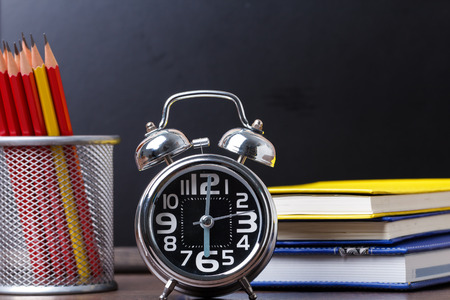 Educational equipment consists of an alarm clock at 6, notebook and pencil placed on a black backdrop study table Archivio Fotografico