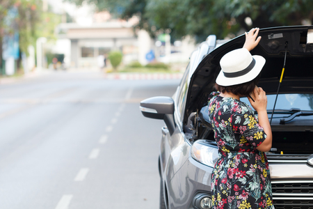 Asian women are using a smartphone to call the insurance company to see the car parked waiting to repair the side. Stockfoto