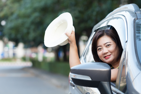 Happy woman with hat in car on relaxing trip