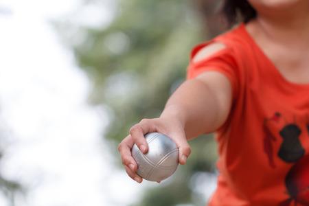 Mano de boule femenino sosteniendo bola o bola de petanque y bolsa para prepararse para un partido