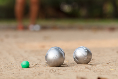 Boules and green jack ball in the match and player in back