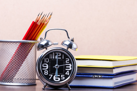 Educational equipment consists of an alarm clock at 6, notebook and pencil placed on a wooden backdrop study table