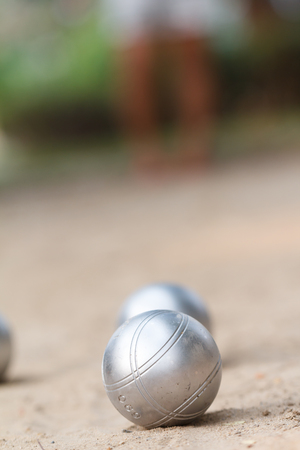 Boules or petanque ball in the match and player in back Stock Photo