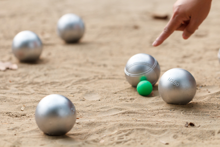boule ball or petanque in match with hand of female boule point in back Banco de Imagens - 92492916