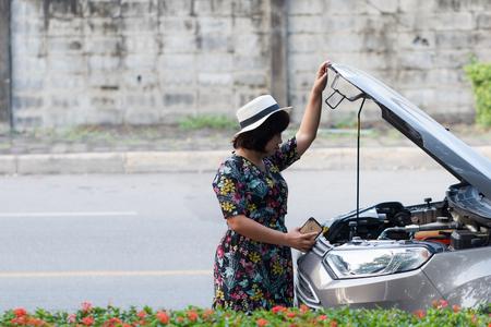 Aziatische vrouwen wachtende verzekeringsmaatschappij om de auto voor reparatie de kant te zien