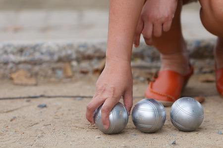 Hand of female boule holding boule or petanque ball in match Stock Photo