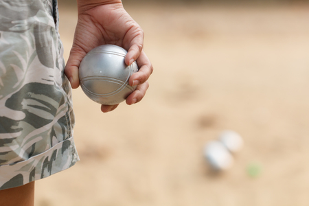Hand of female boule holding boule or petanque ball on match Stock Photo
