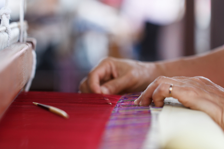 Hand weave silk cotton on the manual wood loom in Thailand, selective focus Stock Photo