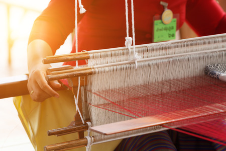 weaving silk cotton on the manual wood loom in Thailand, selective focus