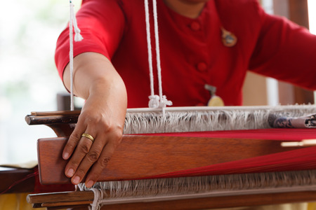Hand of woman weaving silk cotton on the manual wood loom in Thailand, selective focus Stock Photo