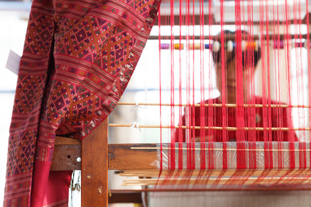 Weaving silk cotton on the manual wood loom in Thailand with woman in back