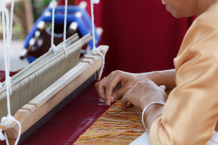 Woman weaving silk cotton on the manual wood loom in Thailand, selective focus Stock Photo