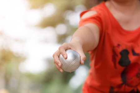 Hand of female boule holding boule or petanque ball and bag to prepare for a match Stock Photo