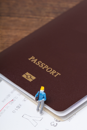Close-up of miniature people with passport and airplane ticket, concept of travel Stock Photo
