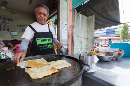 YALA, THAILAND-SEPTEMBER 02, 2018: The trader making Roti with tea and coffee for breakfast, according to the way of Thai Muslim culture on September 02, 2018 in Yala province, Thailand Editorial