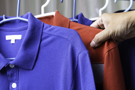 Man hand taking red polo shirt clothes for holiday travel.
