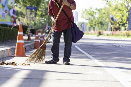 Mann Reinigungspersonal fegt an sonnigen Tagen Müll auf der Straße.