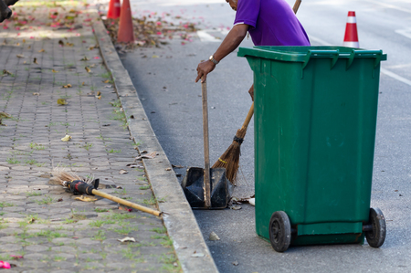 Cleaning worker sweeping garbage on the road, putting green trash.