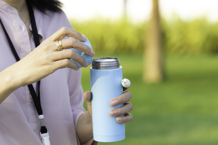 Woman hand holding stainless steel water cylinder with copy space, concept of plastic free.