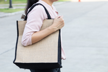 Working woman carry simple flax eco bag with copy space, plastic free concept.