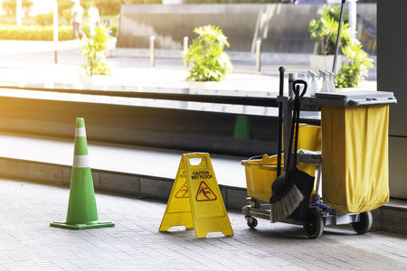 Janitorial and mop bucket on cleaning with caution wet floor.