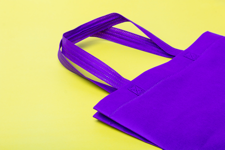 Purple plain flex eco cloth bag with sign of plastic free or no plastic campaign on yellow background with copy space.