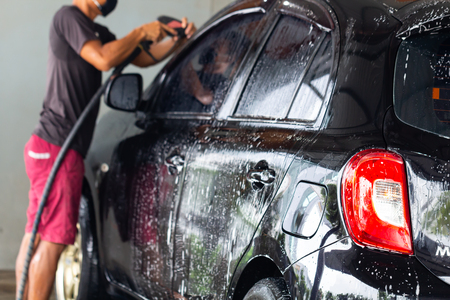 Manual car wash of black car with pressurized water in car wash outside. Stock Photo