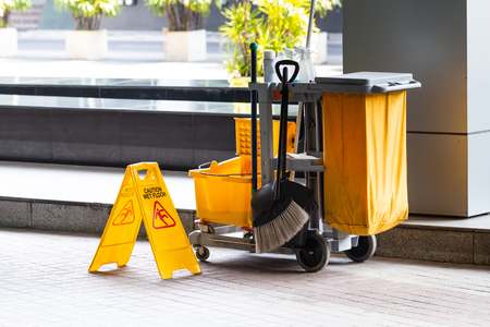 Janitorial and mop bucket on cleaning with caution wet floor sign. Imagens