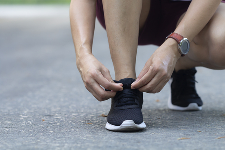 Closeup Asian woman tying her shoes while running on road in the park on morning, healthy concept 版權商用圖片